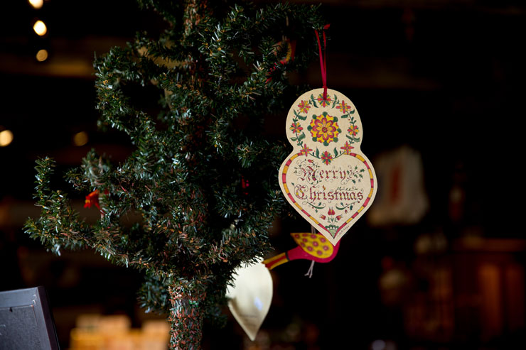 "Pennsylvania Dutch design, hand painted on paper ornament with words reading ""Merry Christmas"" in decorative calligraphy."