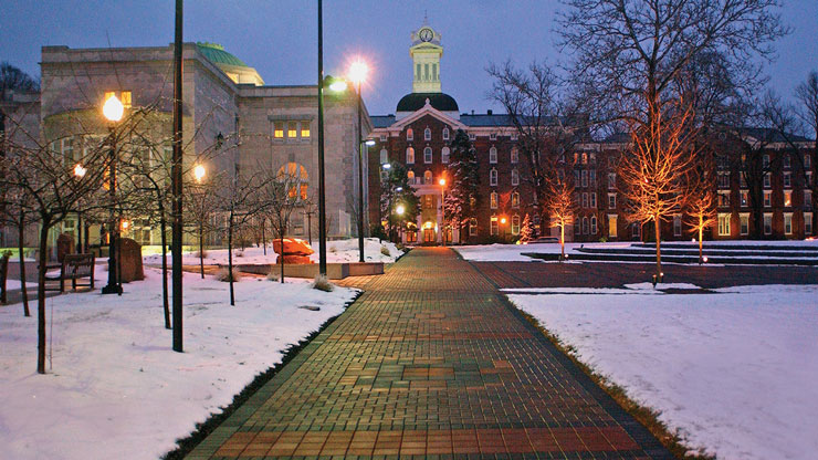 An evening view looking towards Old Main's clock tower from the illuminated brick walkway.
