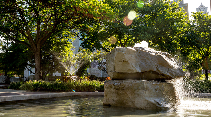 Water splashes over the rock fountain at Alumni Plaza as the summer sun shines down.