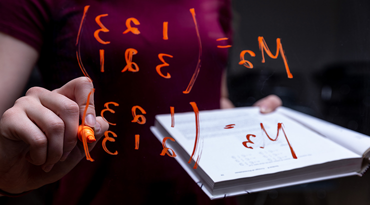 Student writes an equation on a transparent screen with an orange marker.