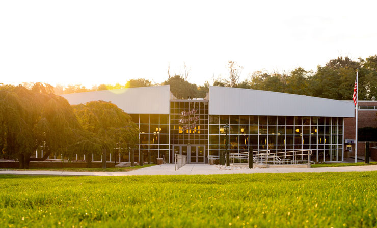 The morning sun casts a golden glow on the windows of South Dining Hall as viewed from the lawn of the DMZ.