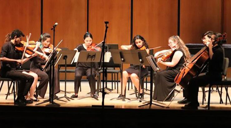 Eight youth orchestra members, seated in a U shape and all dressed in black attire, perform on stage during last year's Summer Music Festival.