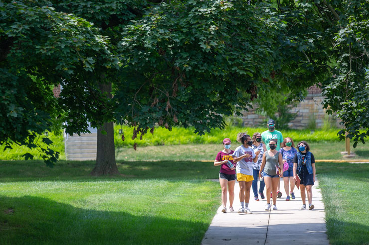 Kutztown University tour guide escorts a group of visitors wearing PPE masks down a campus sidewalk.