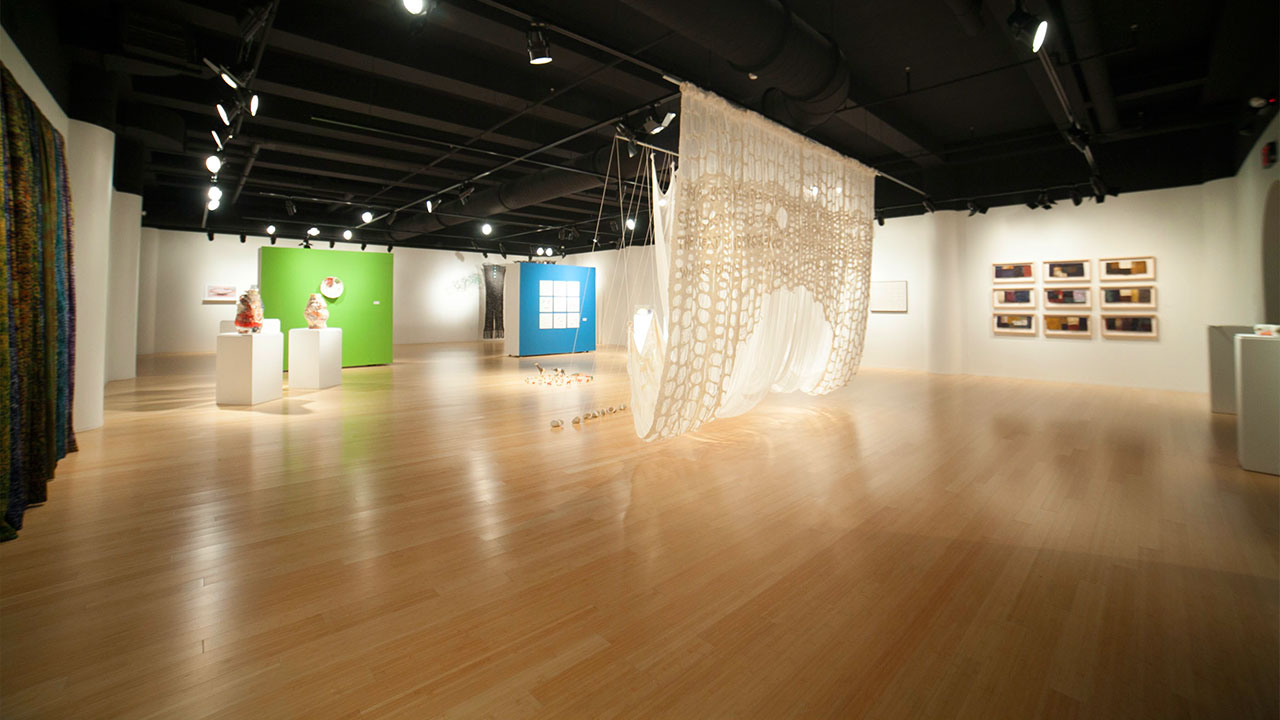 Image of a gallery space with a wooden floor and a black ceiling
