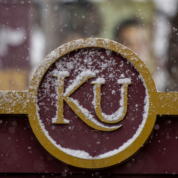 an image of the KU emblem on a street sign on campus with lightly fallen snow in the background and on the shape of the sign.