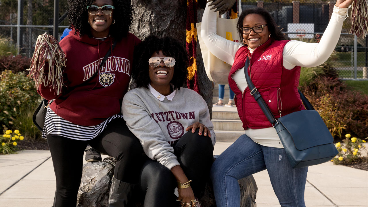 Three Female African Americans demonstrating KU pride by posing together wearing all KU clothing and waving spirit pom poms