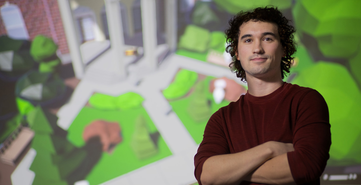 a caucasian male student standing in front of a screen featuring his game design