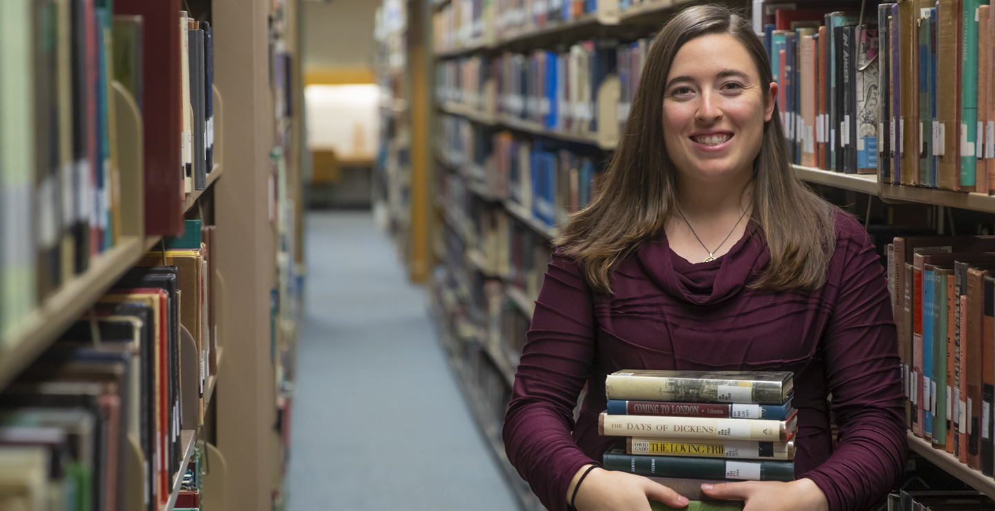 a caucasian female student standing in the rows of books in the library smiling and holding a stack of books