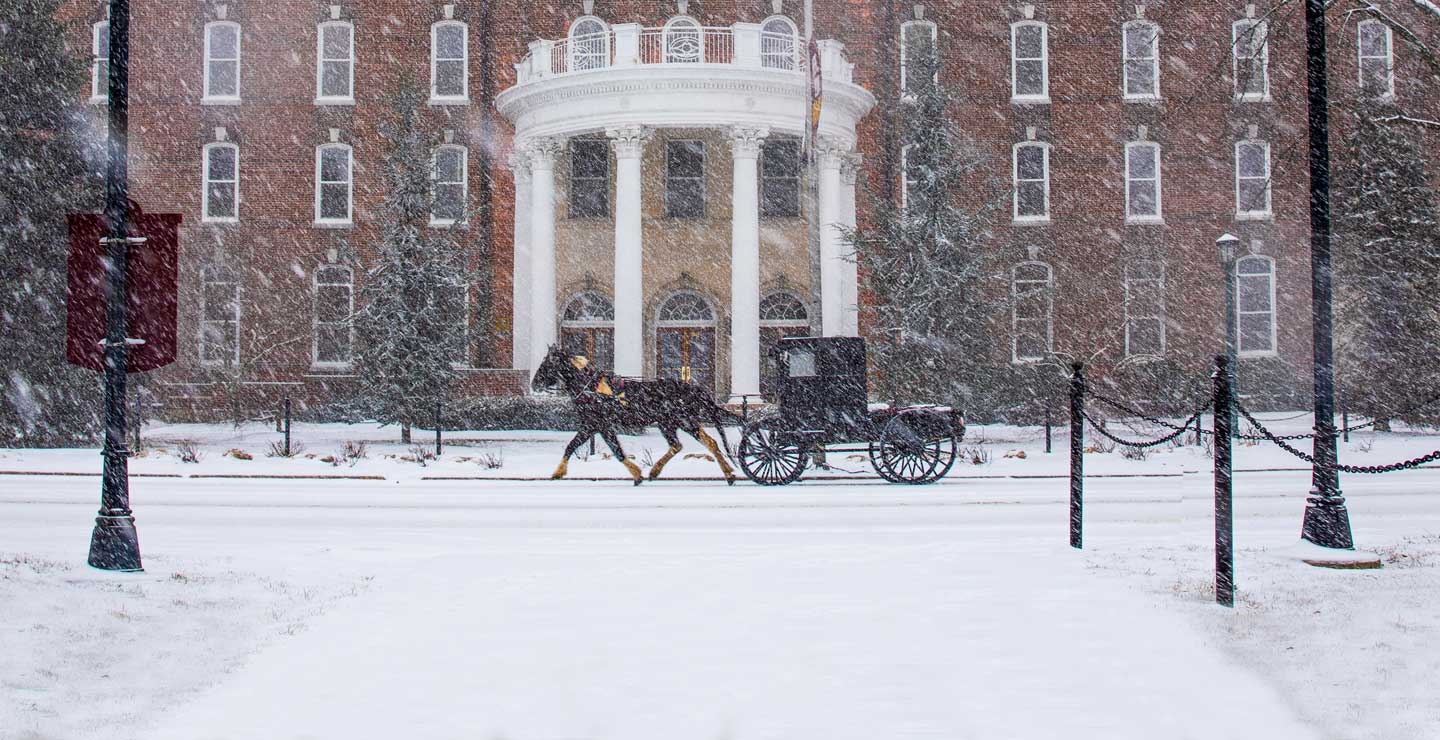 Kutztown University in Winter on a snowy day in front of old main with a horse and buggy trotting down main street