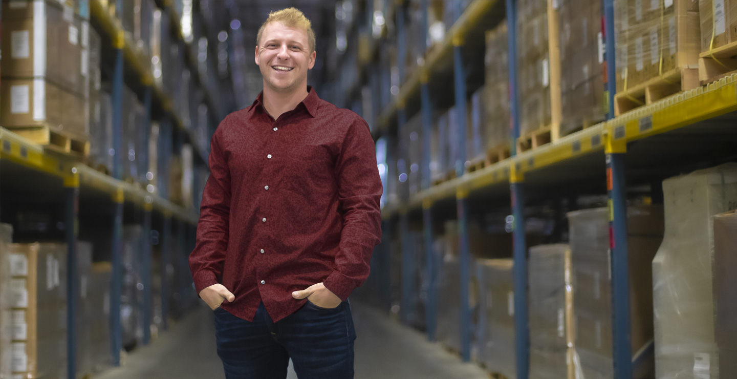 a caucasian male business student standing an smiling between rows of a warehouse