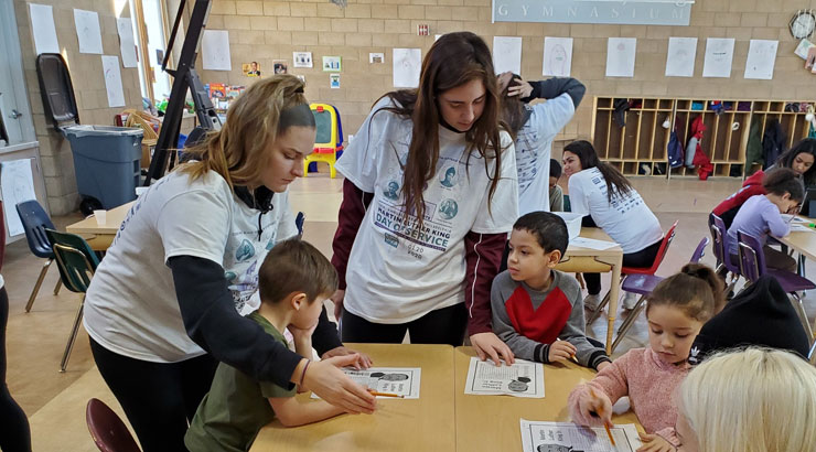 Two KU students assisting children with activities during MLK day of service activities.
