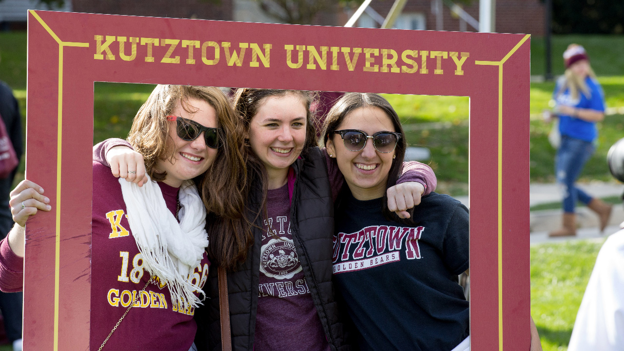 "students posing for a picture inside a ""Kutztown University"" frame"