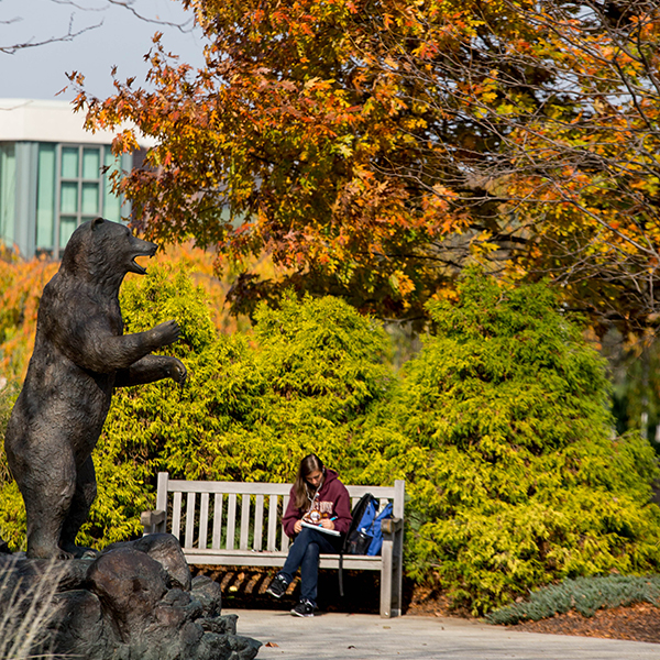 student sitting next to bear statue with fall trees