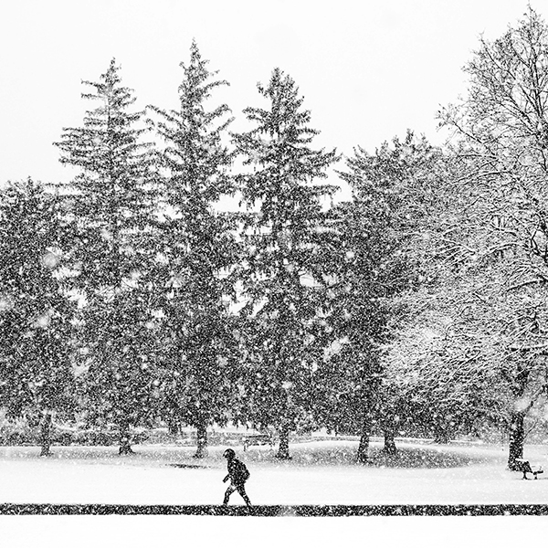 student walking through snow storm