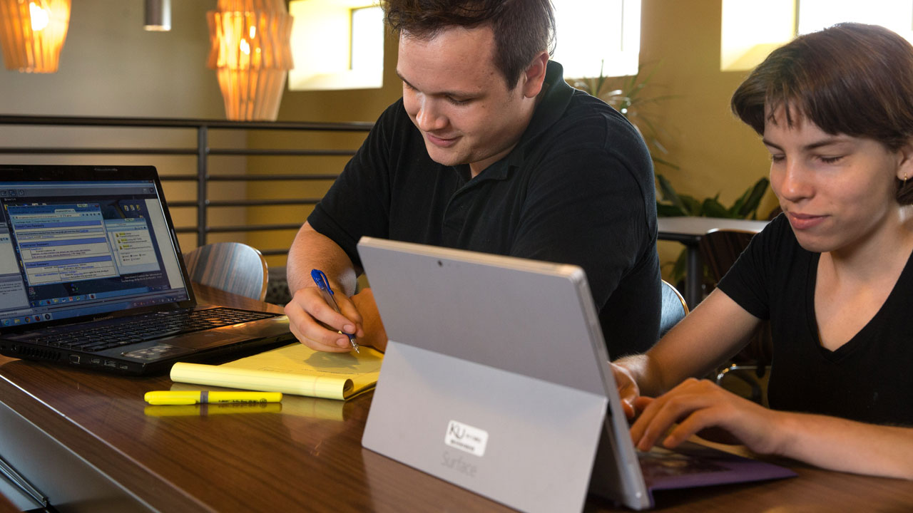 Two computer science students working on laptops.