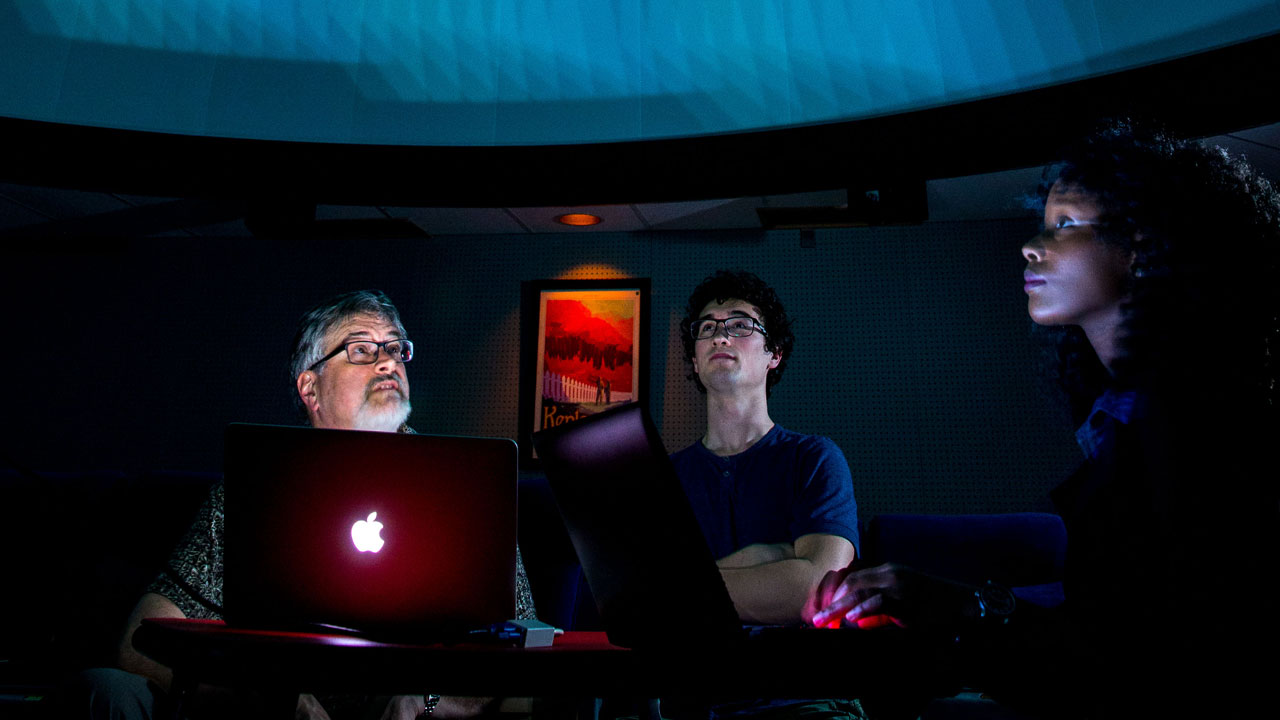 Professor and two students working on computer program in planetarium