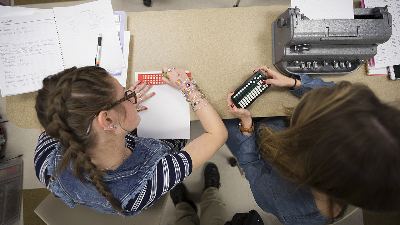 two students working together to learn about braille tools hands-on
