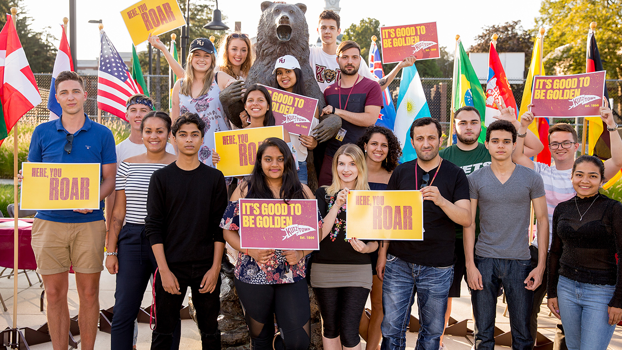 group of students from around the world posing with bear statue holding flags and signs