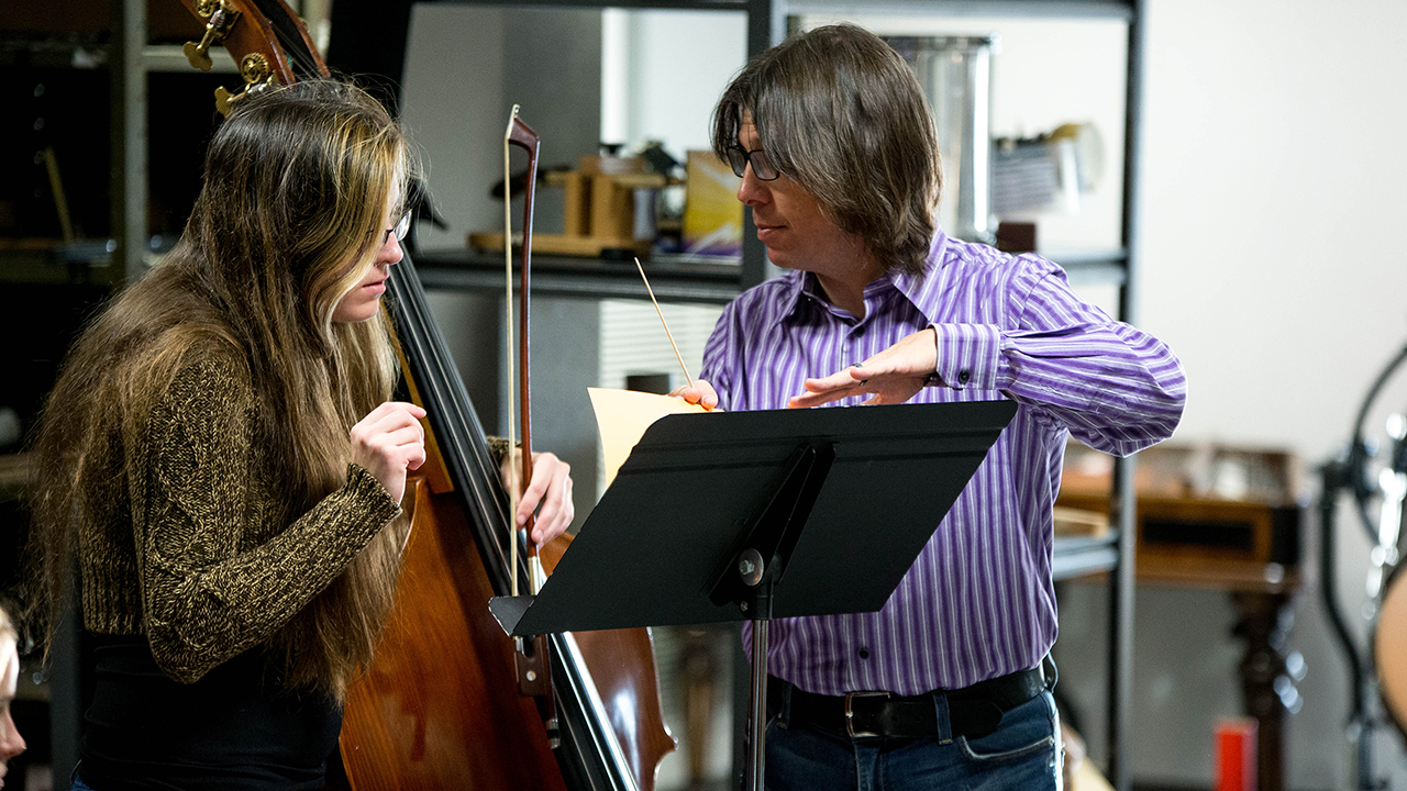 male faculty helping a student with her instrument