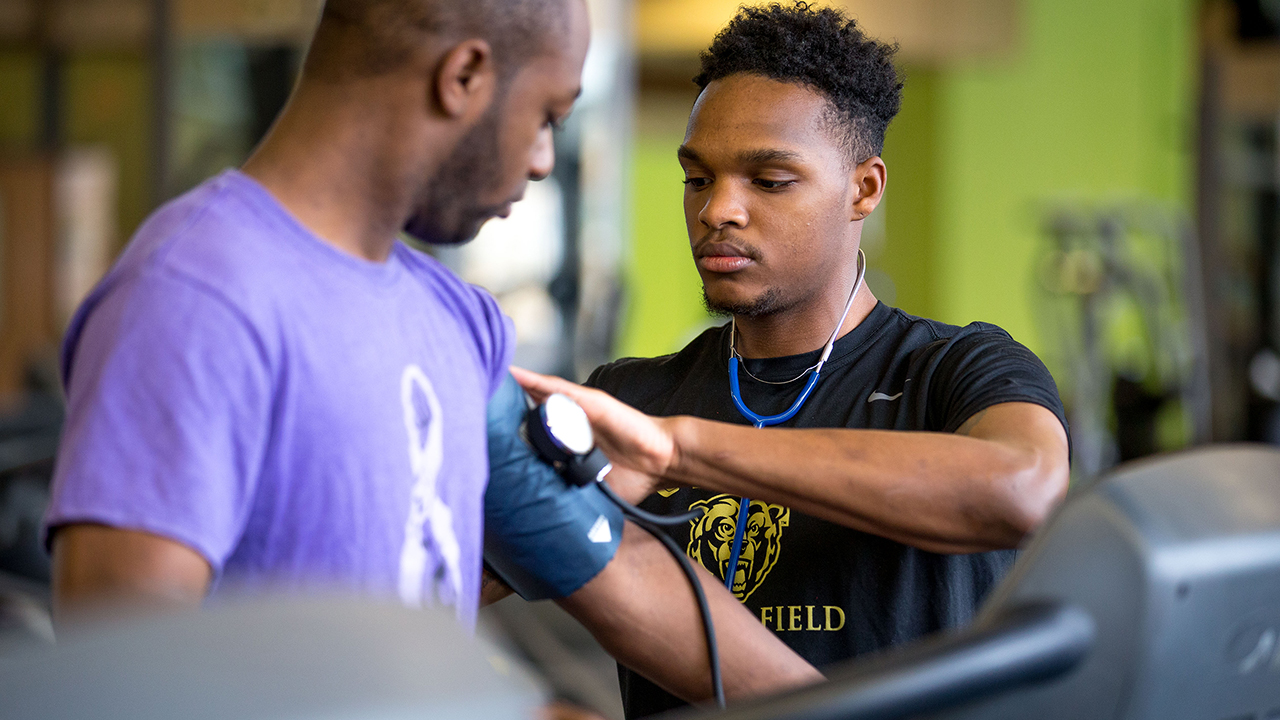 one student checking anothers heart rate on a treadmill