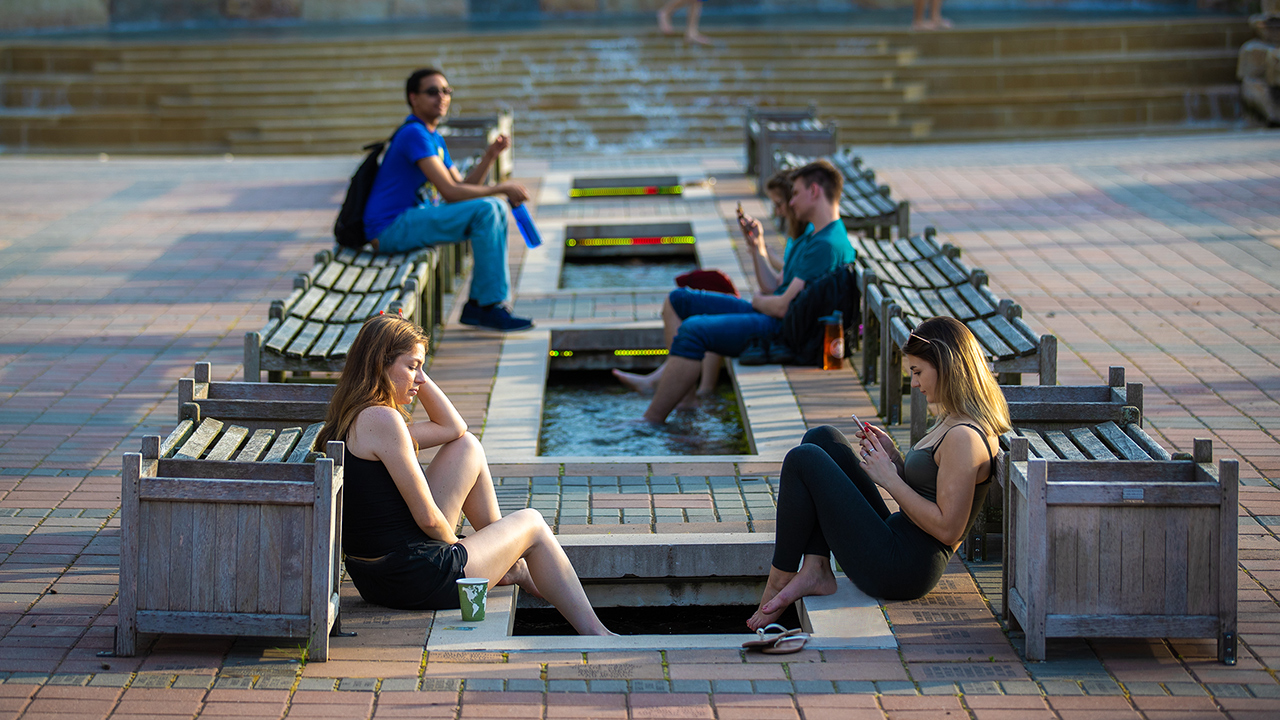 group of students on their phones relaxing at the alumni plaza