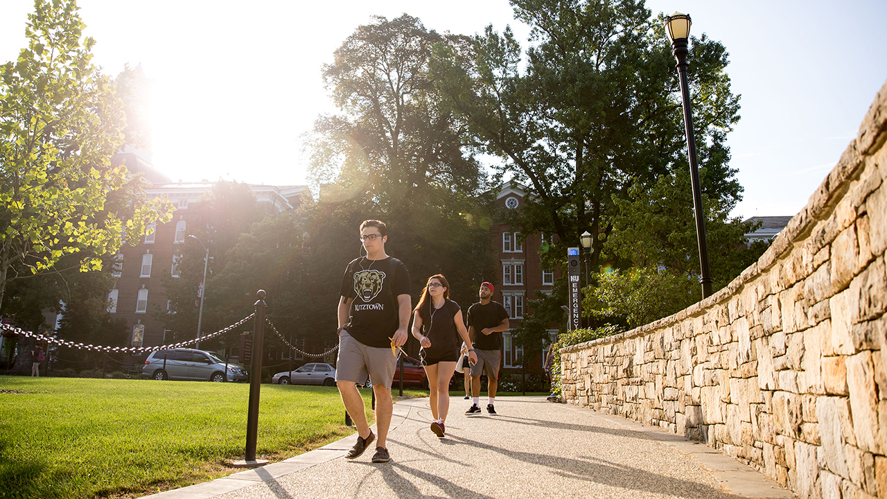 students walking towards the alumni plaza with the sun glaring in the background