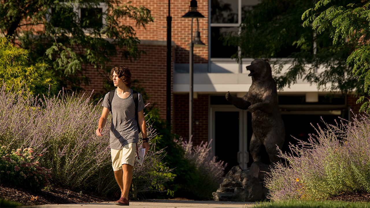 a student walking next to the bear statue