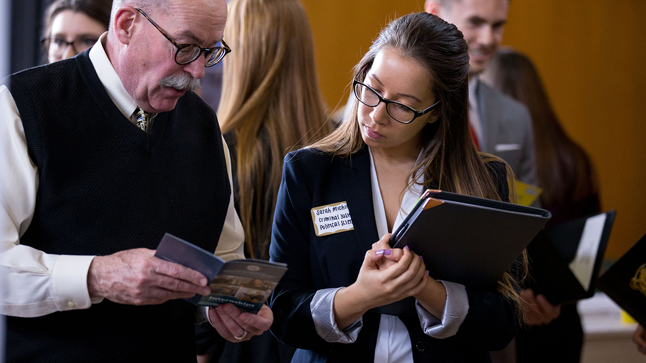 female student holding binder looking at brochure with older male