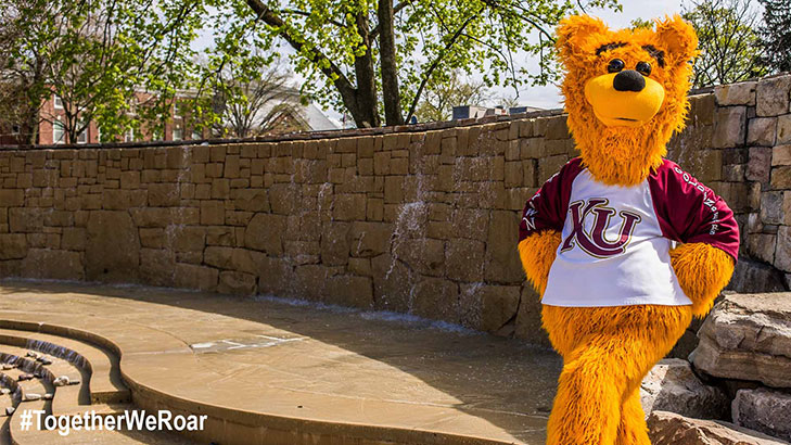 Avalanche the golden bear standing with his hands on his hips in front of the fountain wall on the alumni plaza