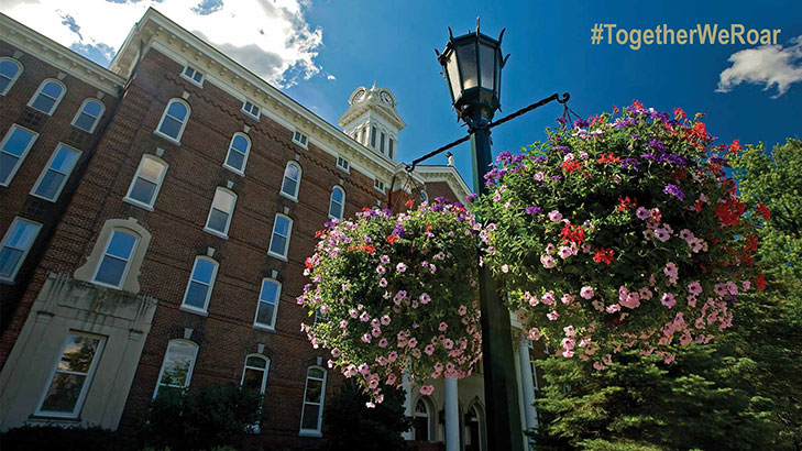 Looking up at the old main clock tower with blue skies and the familiar light post with summer hanging floral baskets