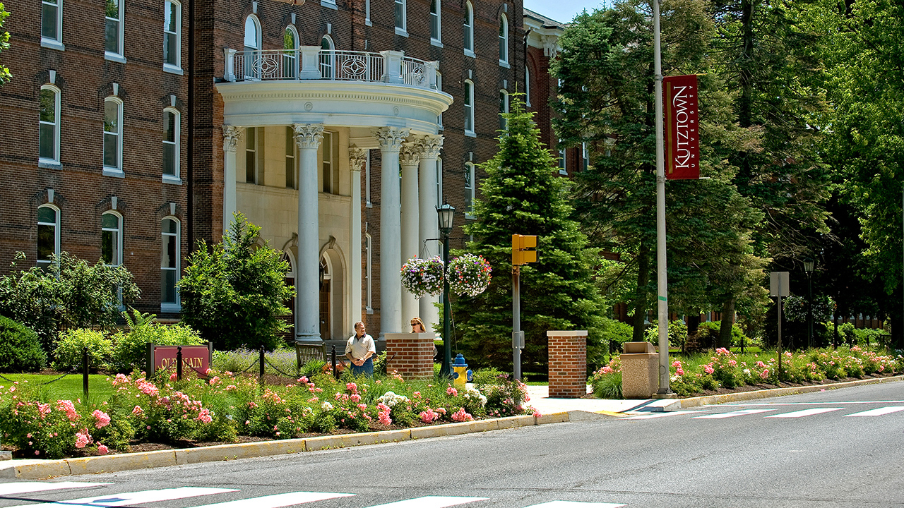 Front quarter view of Old Main and Main Street on a sunny day