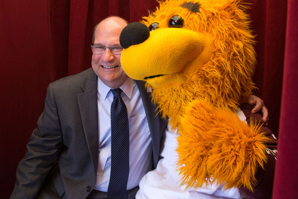 President Hawkinson poses with Avalanche the golden bear for a photo in a photobooth