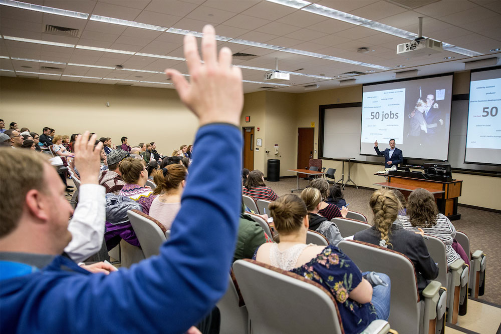 Students in classroom with hands raised, professor at front of the room in front of screen with words and photos.
