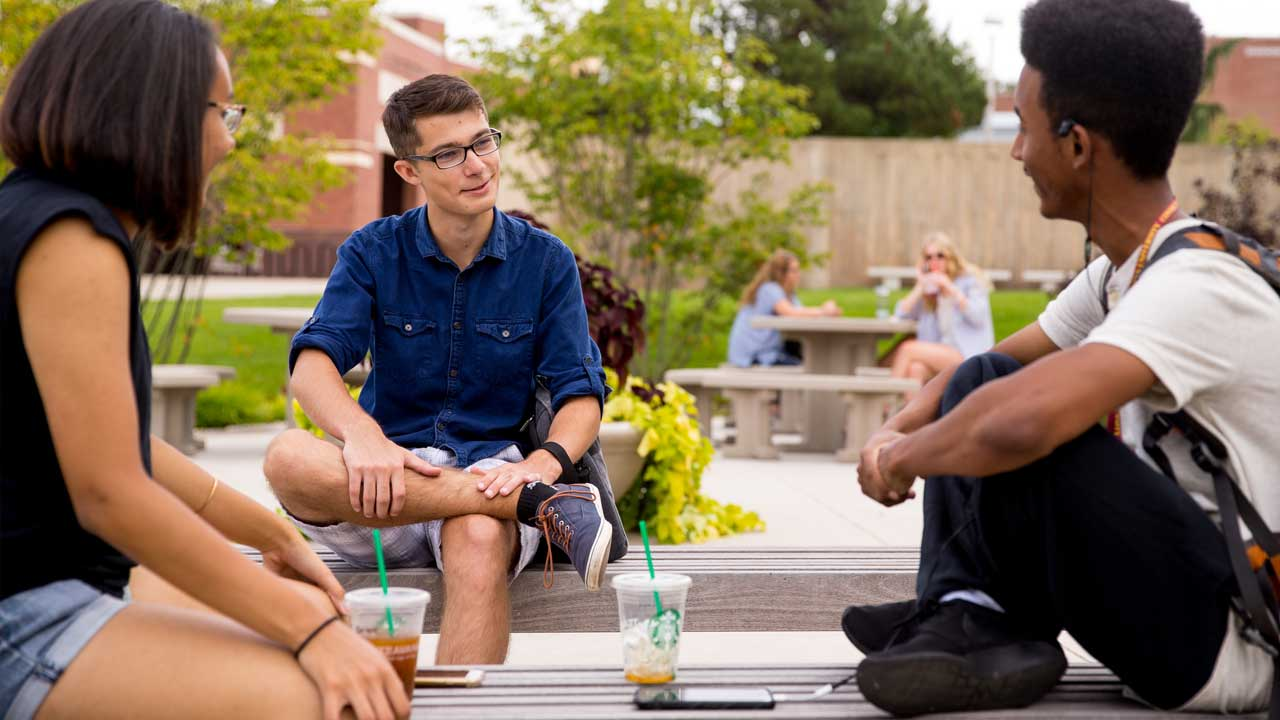 Three students, one female, two male, conversing in an outdoor gathering space on campus at kutztown university